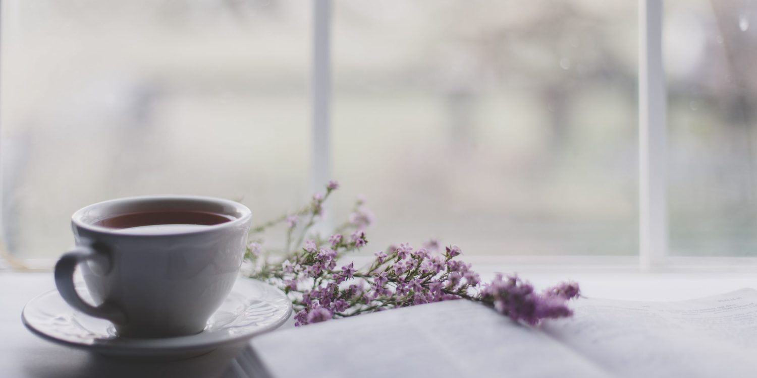 small cup of coffee next to a pink flower laying across an open book.