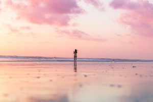 Pink sunset over the ocean with a girl by herself in the background.