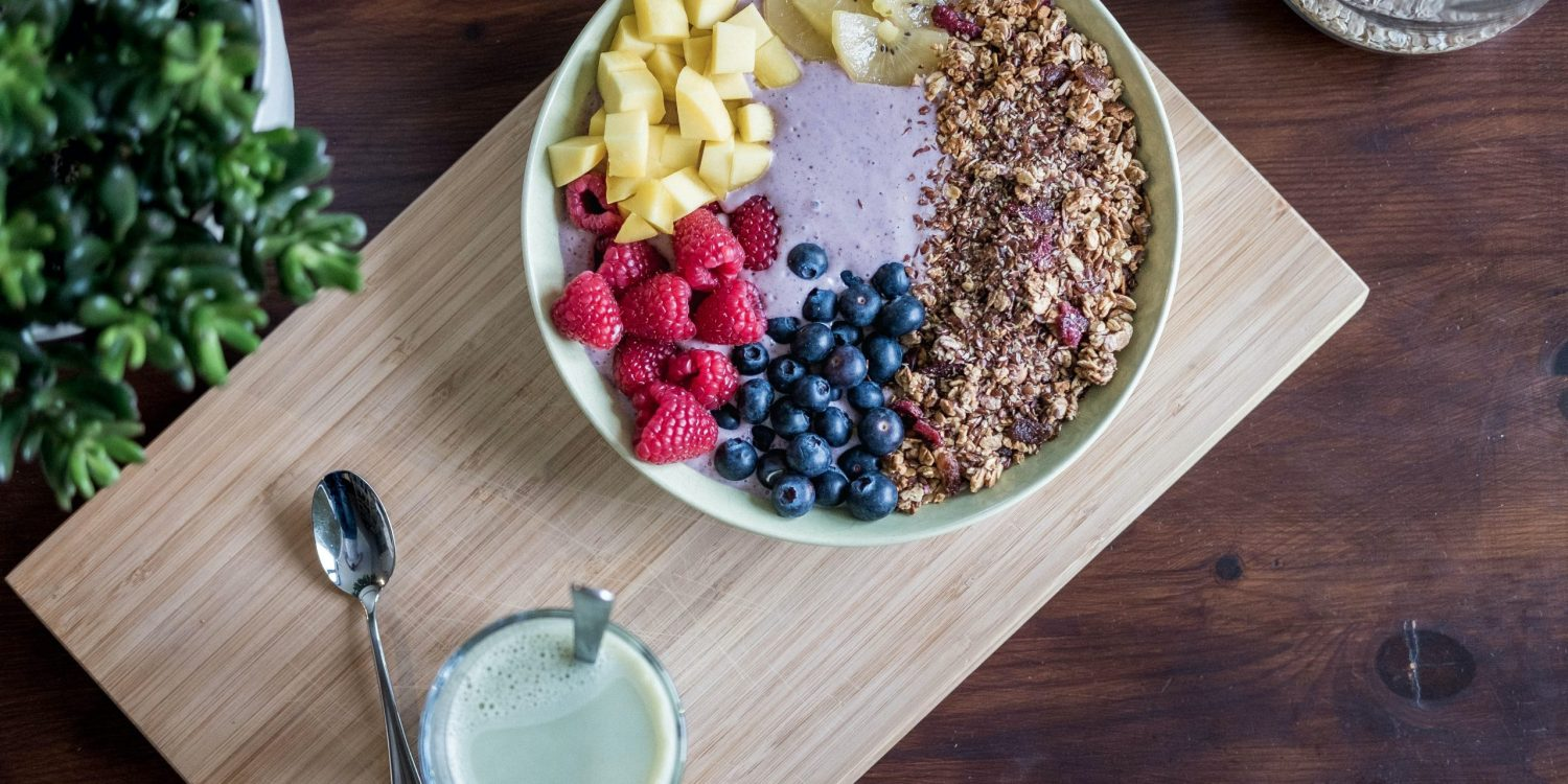 A smoothie bowl topped with pineapple, raspberries, blueberries, and granola on top of a cutting board with a spoon on the side.