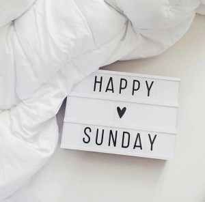 Happy Sunday board on a white background next to a white blanket.