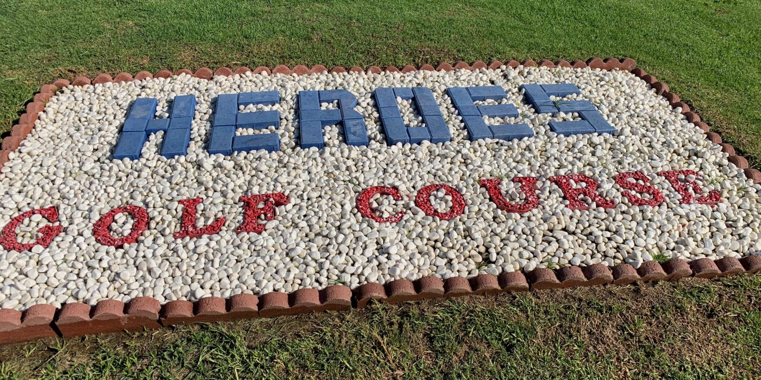 A rock memorial that says Heros Golf Course.