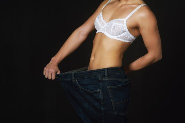 Girl shows her weight loss , old jeans