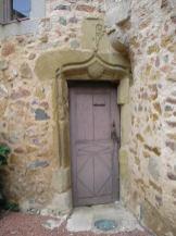 Entrée du prieuré - au-dessus les armoiries des bénédictins, le blason et la crosse de l'abbé