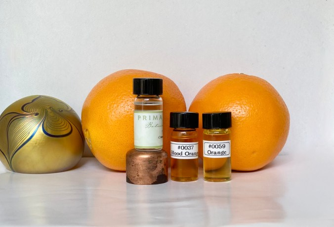 Photo of cold-pressed oils of Orange and Blood orange with some fruits and a art nouveau paperweight.