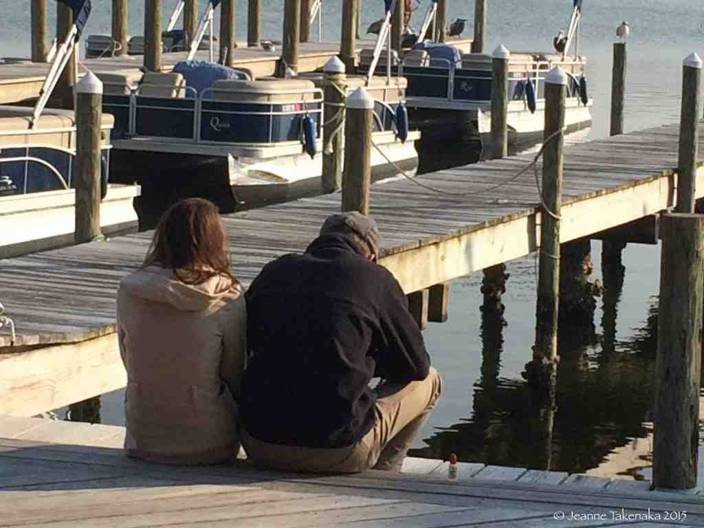 A couple sits on a dock, quiet
