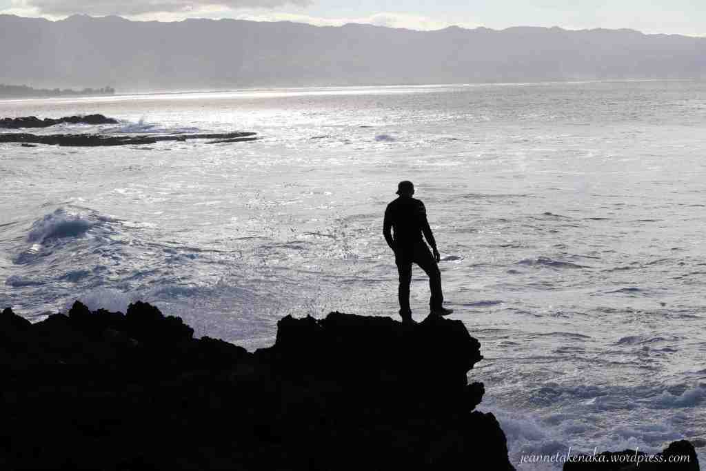 Silhouette of a man standing on rocks over the ocean and contemplating something