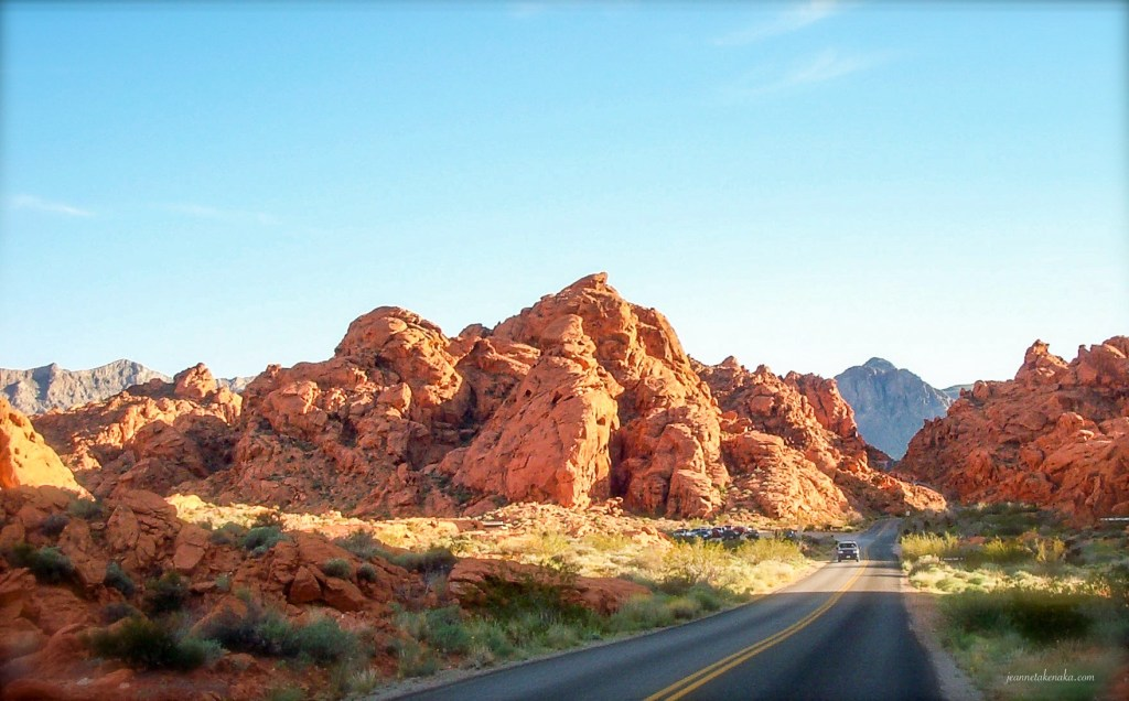 Two lane highway through the desert with red rocks on each side of the road