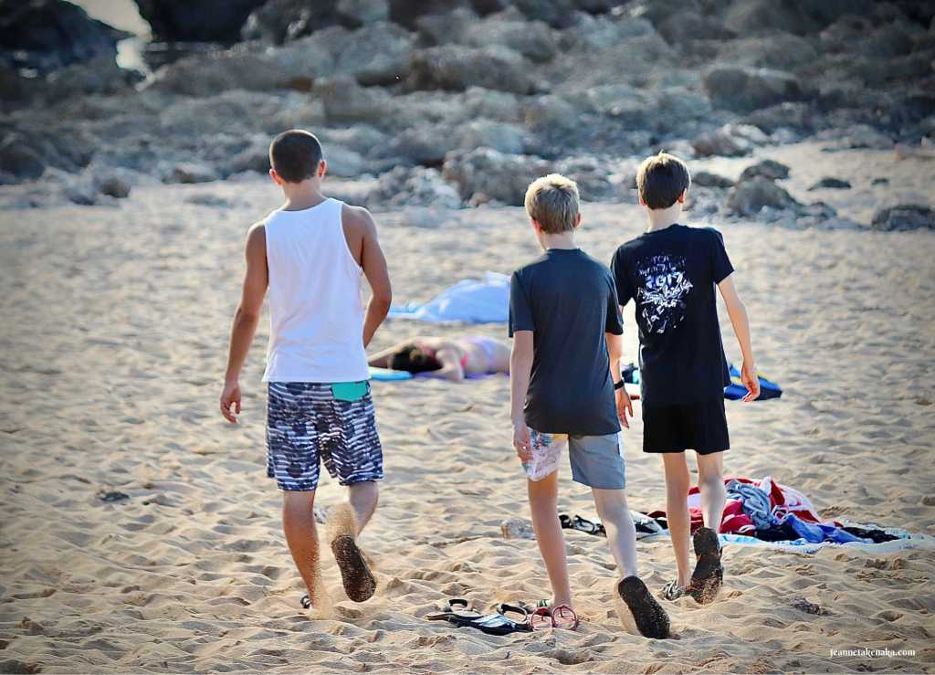Three young men walking together on the beach building relationship