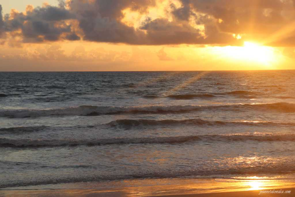 An orange sunrise reflecting on the ocean waves as they roll into shore