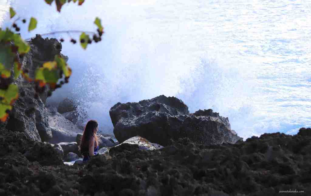 A woman standing among rocks as waves crash nearby