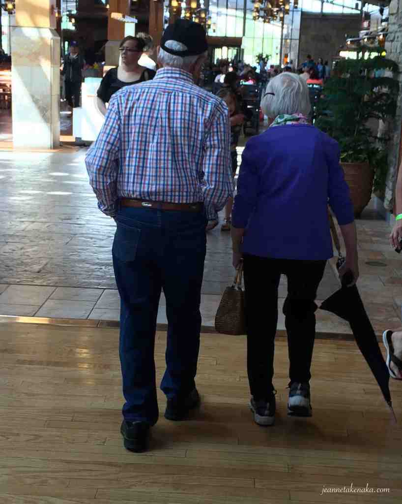 An older couple walks together in a mall