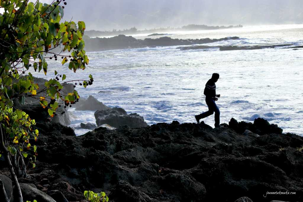 Silhouette of a man walking on rocks above a churning ocean