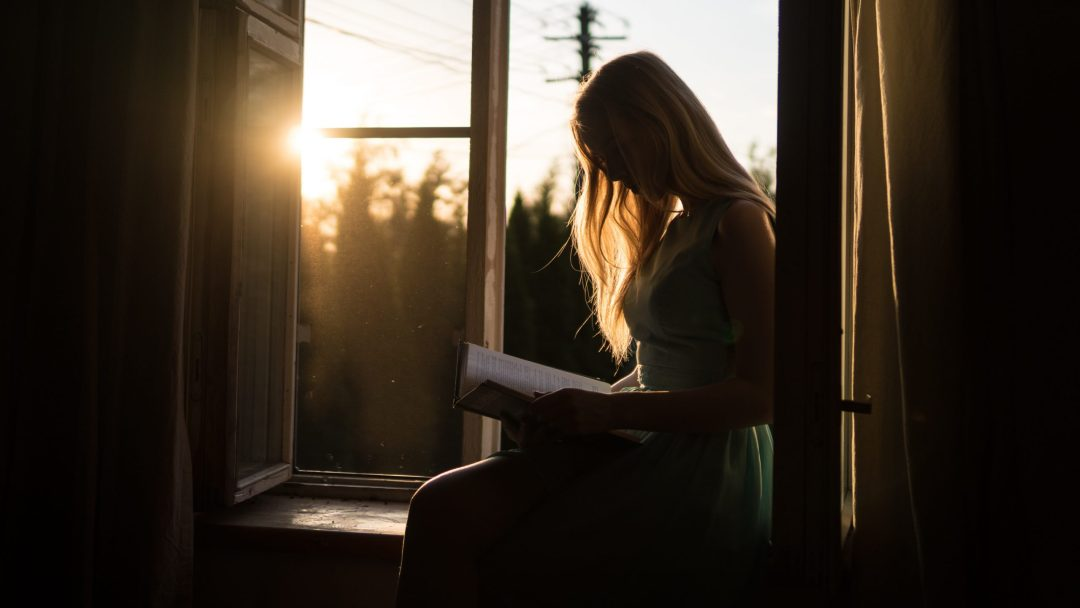 girl by window reading the promises of God from the bible
