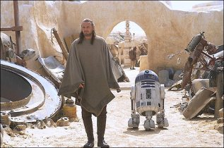 Qui-Gon (Liam Neeson) and R2-D2 scour Watto's junkyard on the desert planet Tatooine. Web grab from www.ew.com./ Photograph: Keith Hamshere/Lucasfilm Ltd. Web grab from www.ew.com./ Photograph: Keith Hamshere/Lucasfilm Ltd. & TM All Rights Reserved