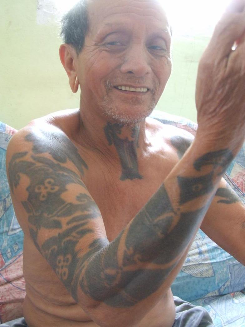 An elderly gentlemen from one of the longhouses near Bukit Sadok showing off his tattoos.