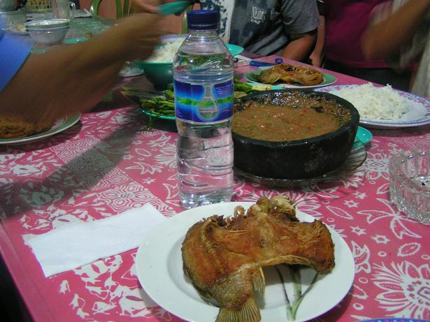 Deep fried fish and very hot tomato sambal in the background.
