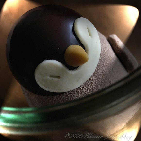Egguin, the penguin Easter egg by Soma Chocolate with lights aimed at its face from all four corners.
