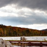 Noyes pond with fall foliage showing good color and dramatic clouds above with sun streaming in