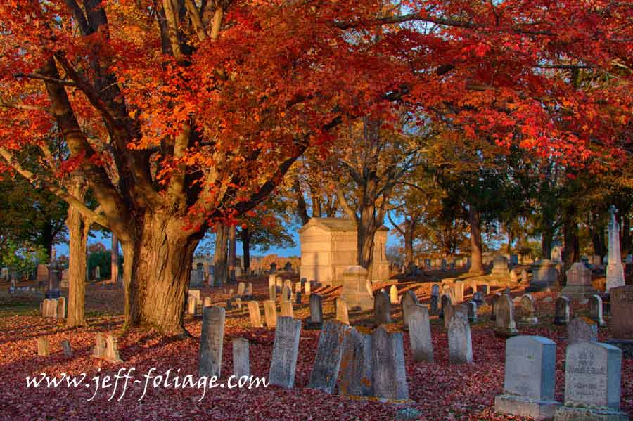 Fall foliage shot in Dover cemetery in New Hampshire. The late afternoon sun reaches out across the cemetery stones with the final suns rays.