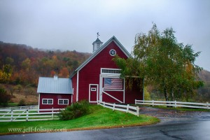 In Pomfret VT a red barn with an American flag on it  sit amid fall foliage