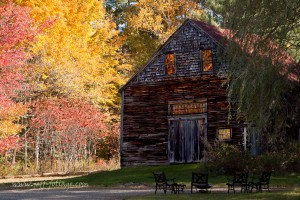 A barn in Ossipee New Hampshire is surrounded by bright red and yellow fall colors