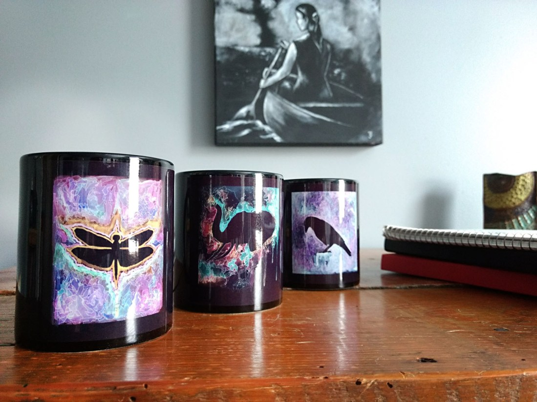 Three black coffee mugs lined up on a table. One has a colorful purple and gold painted dragonfly. The second has a colorful teal and fuchsia elephant. The third has a grey and lavender raven. Made by Jeffcoat Art. $25 a piece.