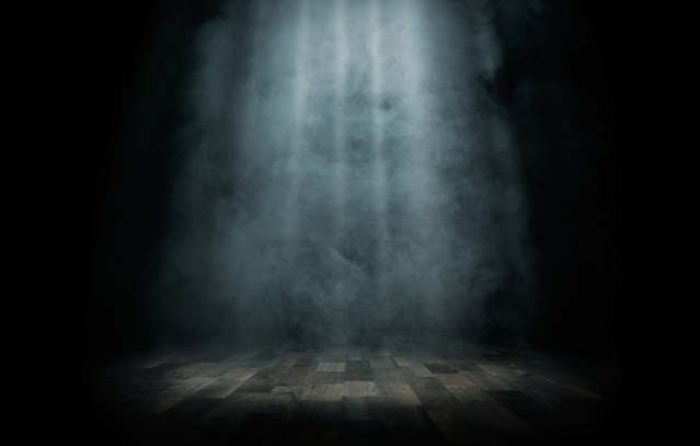 A dark room with a faded spotlight shining on an empty stage floor