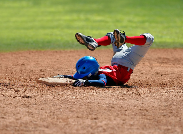 young baseball player sliding head first into second base