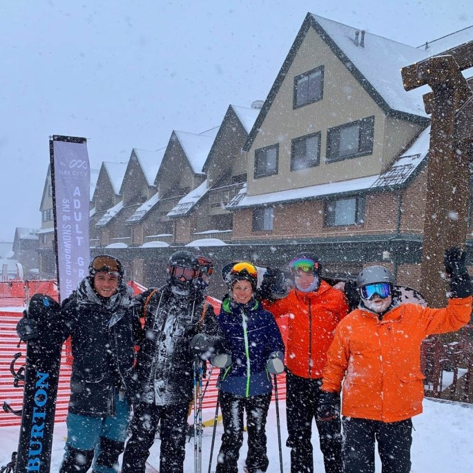 5 people on skis and snowboards standing in falling snow at a ski resort