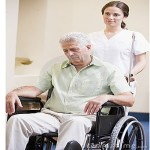 An older man in a wheelchair looking sad being pushed by a disaffected nurse
