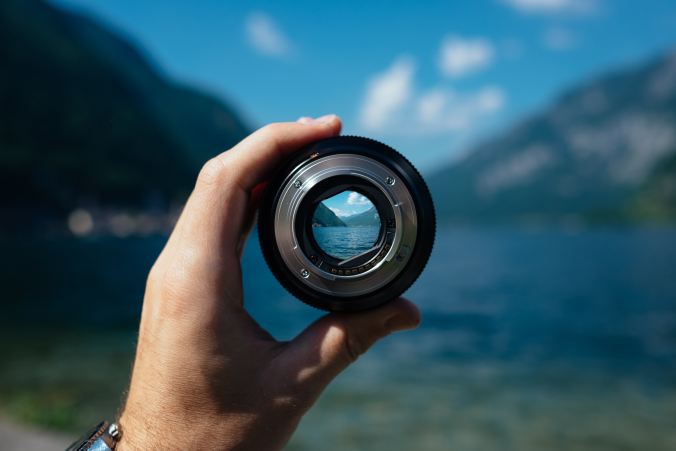Image of a man's hand holding a camera lens in front of a landscape, through which the scene can be seen in focus