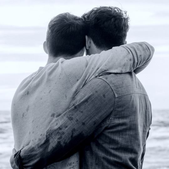 Photo of two men from the back, embracing and staring out to sea