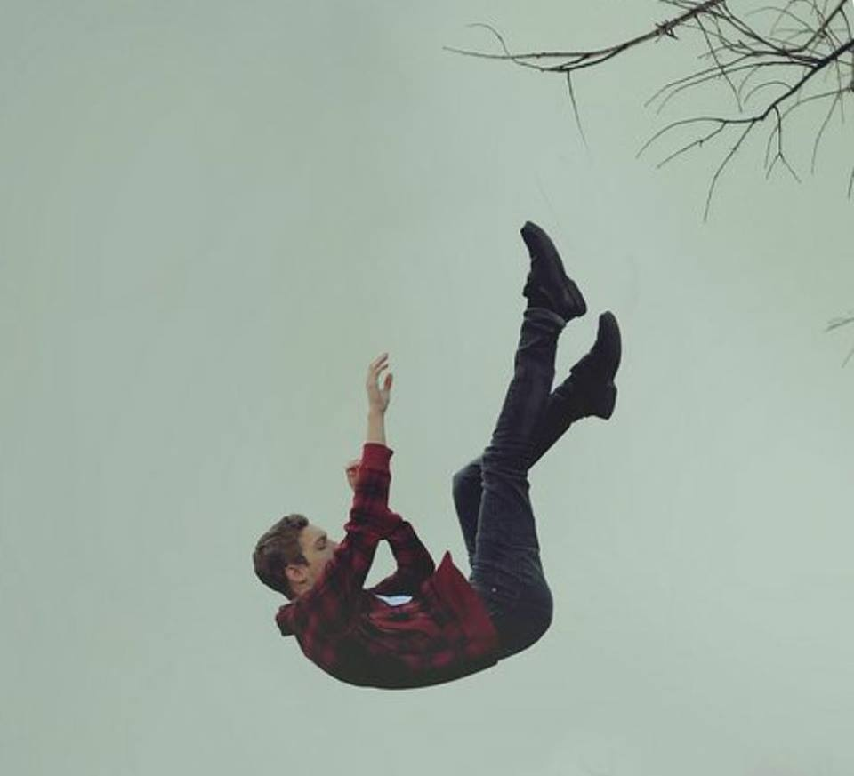 Photo of a boy falling through the air with a tree branch in the upper righthand corner.