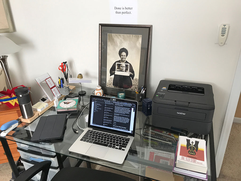 "A photo of my desk with the words ""Done is better than perfect"" printed and taped to the wall above it."