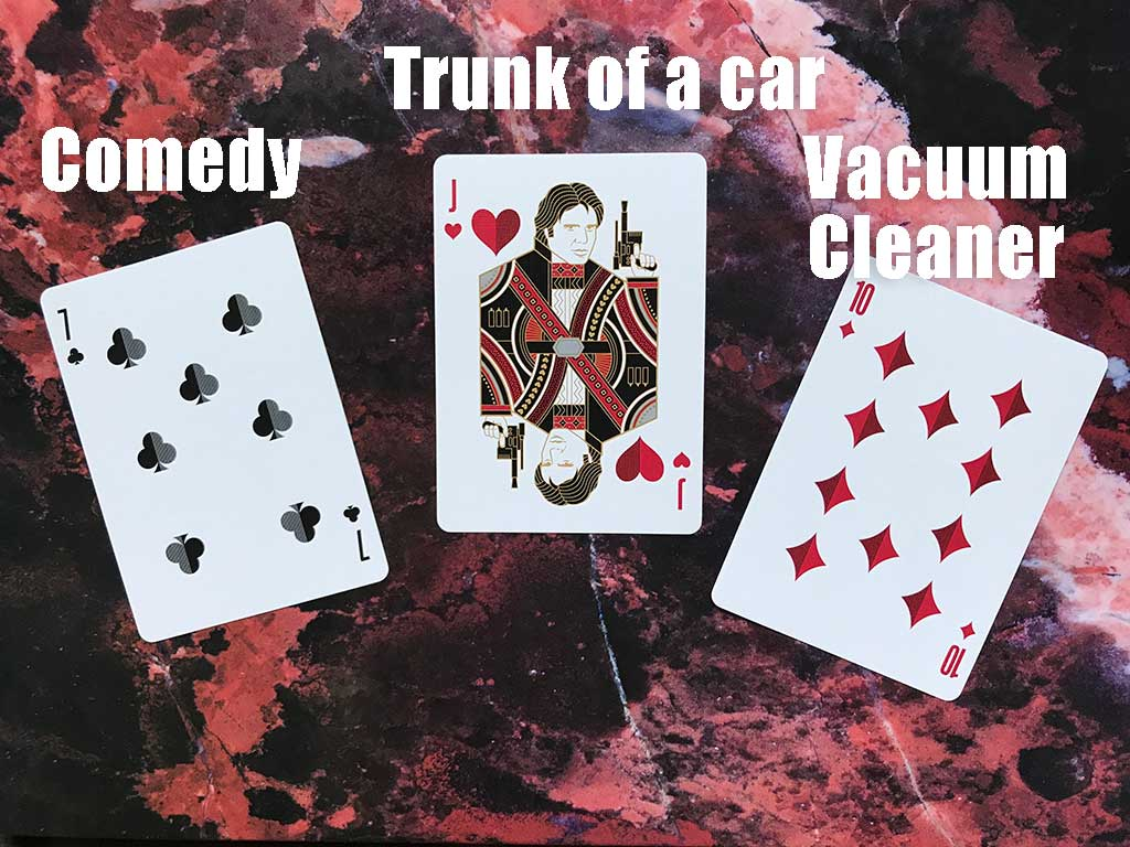 """Flash Fiction Draw for July 2021: Three playing cards are shown, a 7 of clubs, a Jack of hearts, and a 10 of diamonds, with the words """"comedy,"""" """"trunk of a car,"""" and """"vacuum cleaner"""" superimposed over the image."""