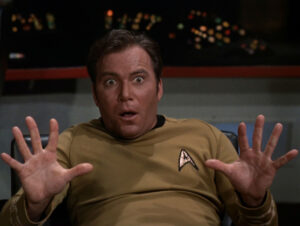 Captain Kirk holds his hands up in surprise