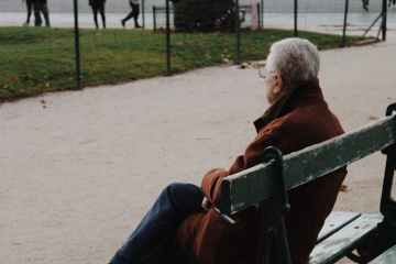 elderly man sitting on bench in park during autumn day