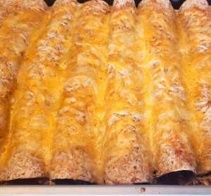 turkey enchiladas with ground turkey, black beans, fire roasted corn, enchilada sauce, salsa, cheese, and taco seasoning