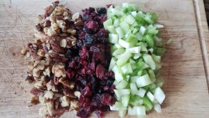 cut up walnuts, craisins, and celery for the cranberry walnut chicken salad