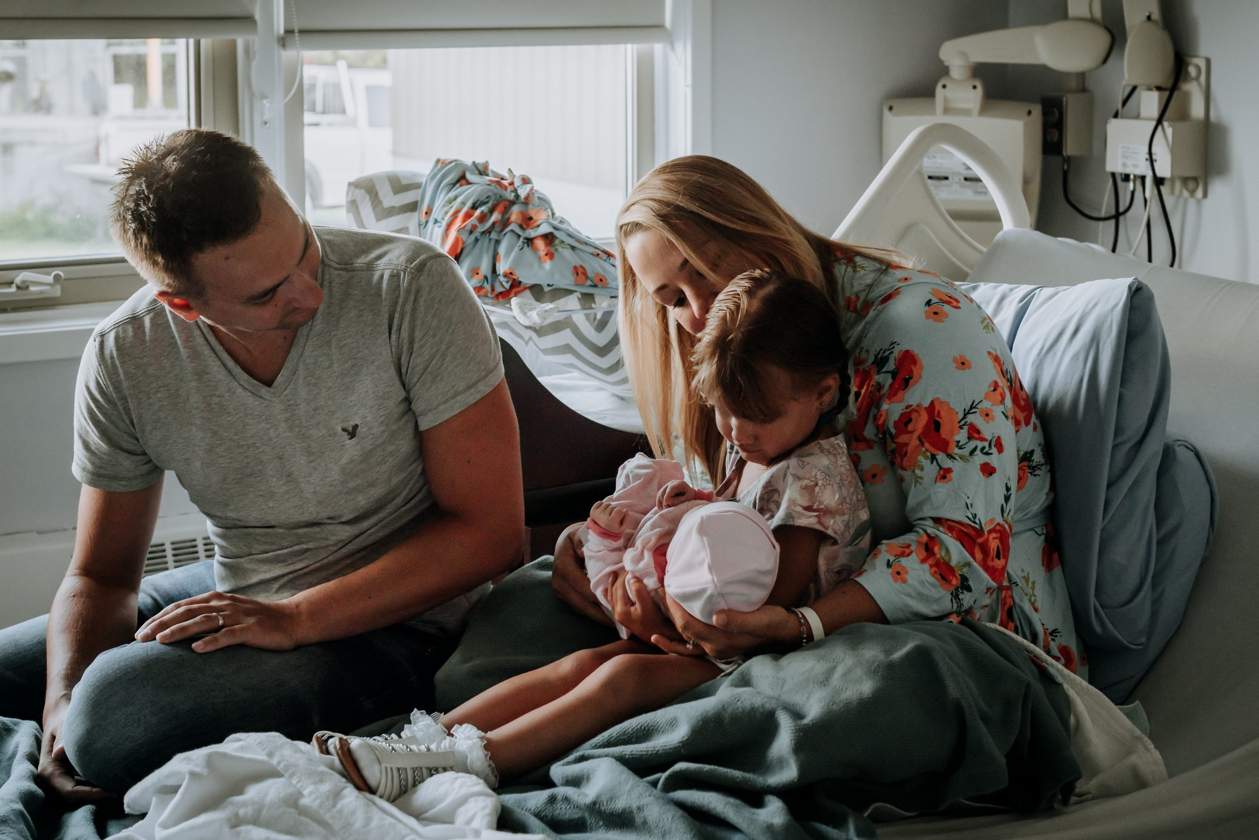 Family sits together in a hospital bed helping their toddler hold their new baby image taken by birth photographer jena lee photographs in golden bc