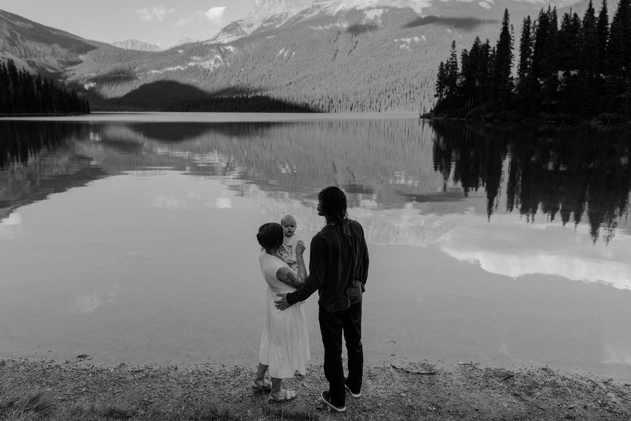 A black and white photo of two parents holding their baby with a beautiful mountain view in the background during their family photography session at emerald lake with jena lee photographs