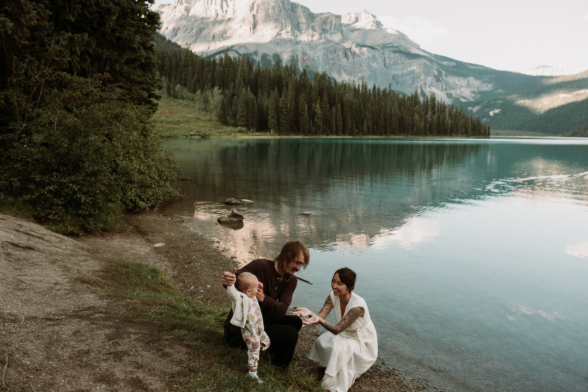 Two parents hold their toddlers hand walking on the beach during their family photography emerald lake with jena lee photographs
