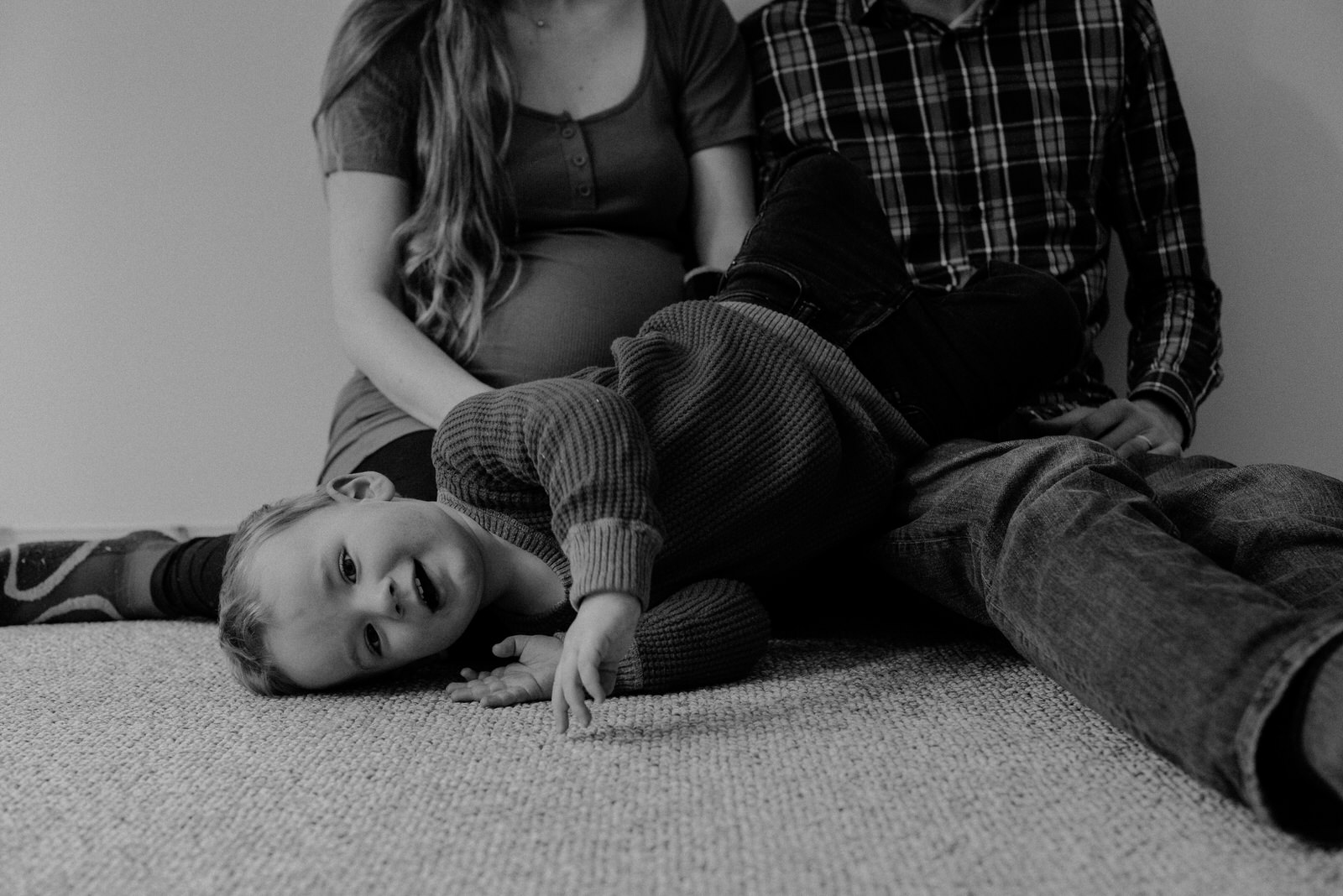 Black and white photo of a toddler laying on his parents lap with his mothers pregnant baby bump visible in the background taken by maternity photographer canmore jena lee photographs