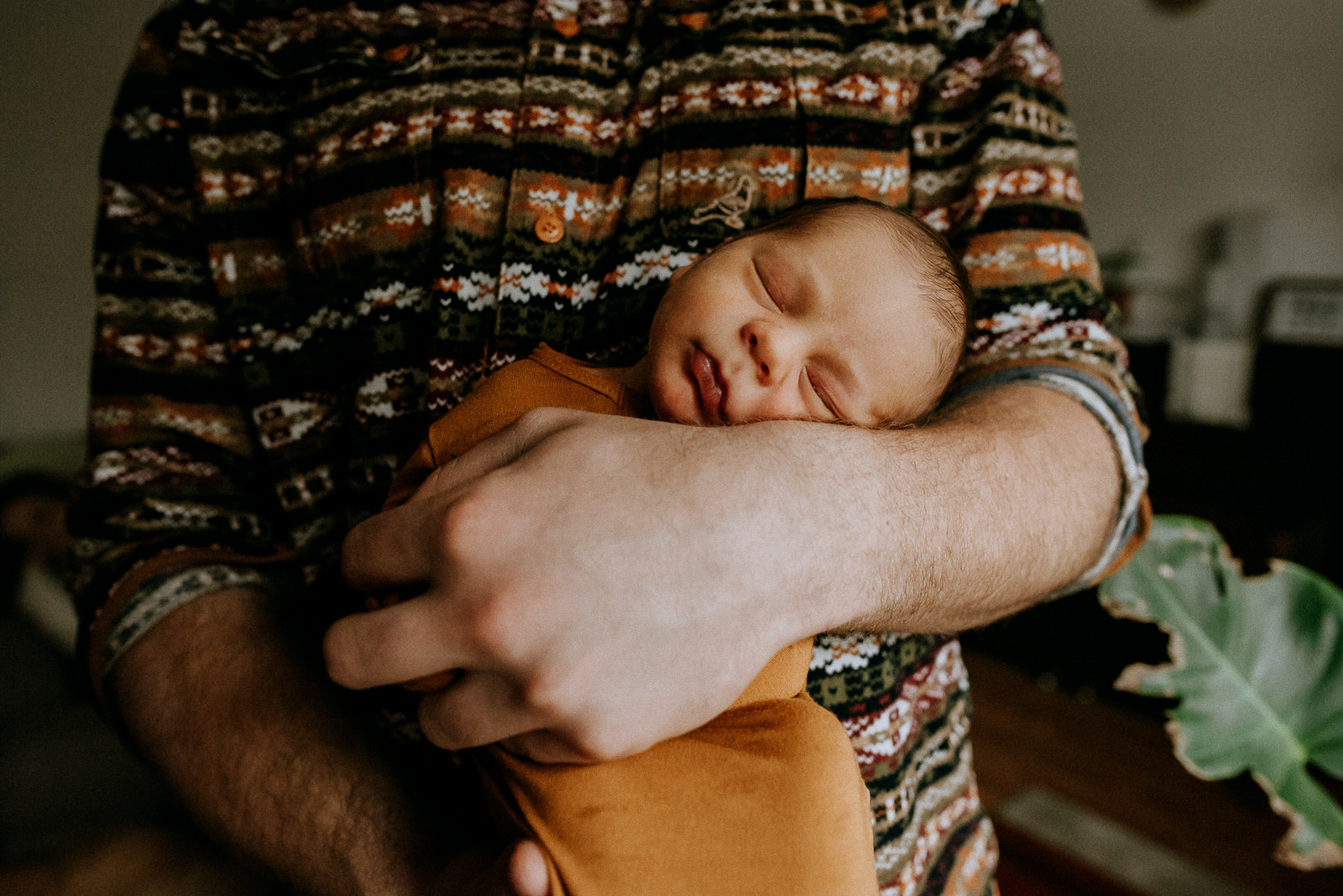 Close up of a dad holding his baby on his chest inside their living room during a lifestyle newborn photography session in golden bc with jena lee photographs