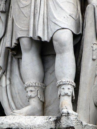 Toeless dog socks on a statue.