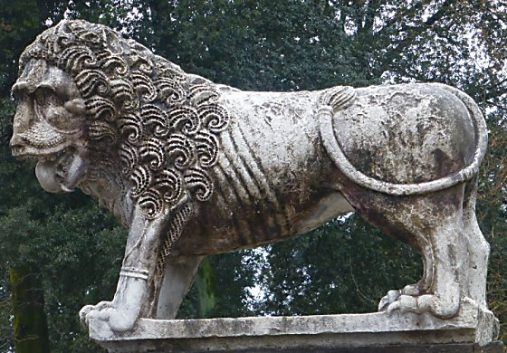 Lion statue with curly mane and tongue hanging out.