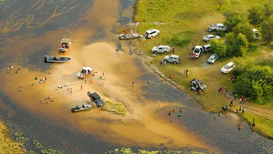People swimming and boating in a river near Maun, Botswana.