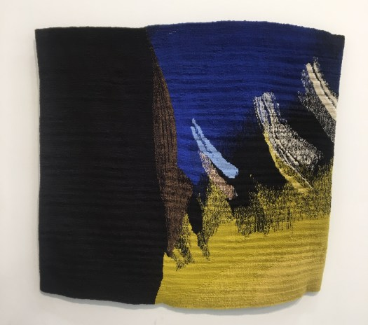 Handwoven tapestry wall hanging in blues and yellows, displayed on a white gallery wall.