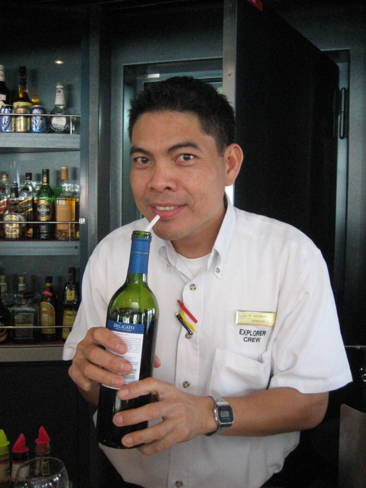 MV Explorer crew member drinking wine with a straw