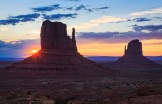 The sun rises behind the iconic Mittens of Monument Valley.